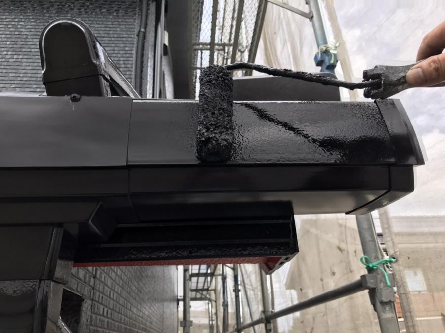 大きめの雨樋にローラーで黒色を塗布する職人