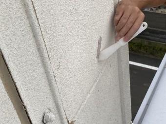 白いへらで外壁のクラックに変成シリコンをのばすスタッフ
