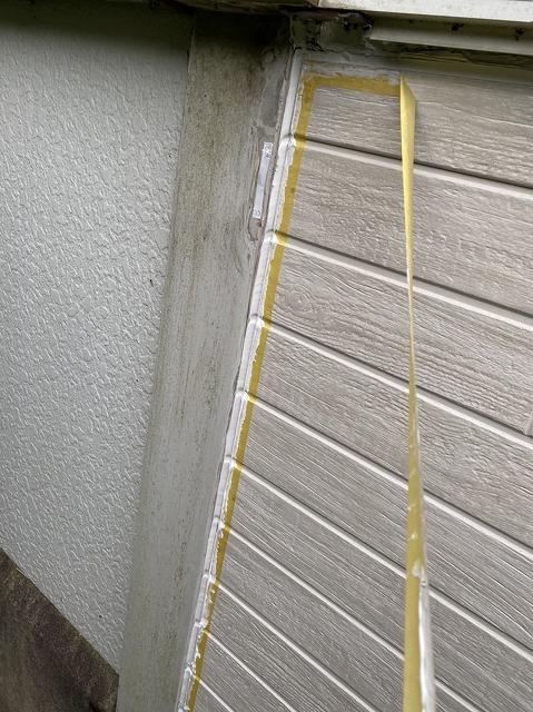 サイディングの縁にコーキングを施しマスキングテープを剥がす
