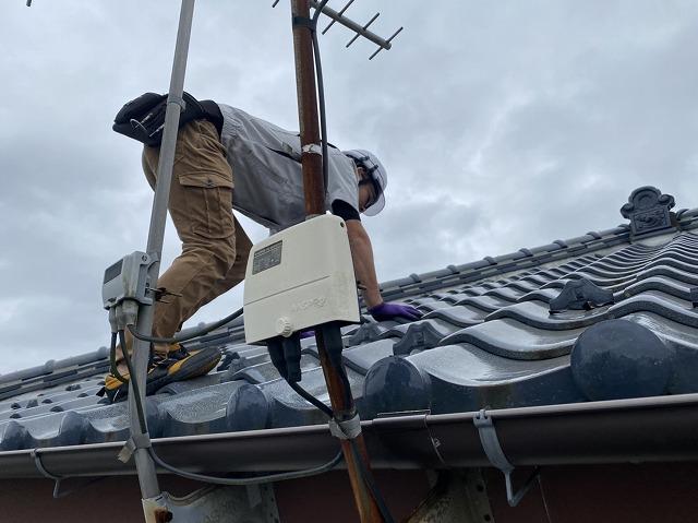 四つん這いになりながら瓦屋根を上るスタッフ