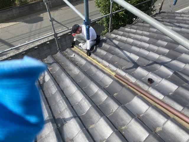 大きな下屋根に這樋を施工する為に計測する職人