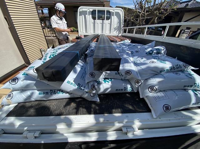 トラックに積まれた袋に入った漆喰や垂木