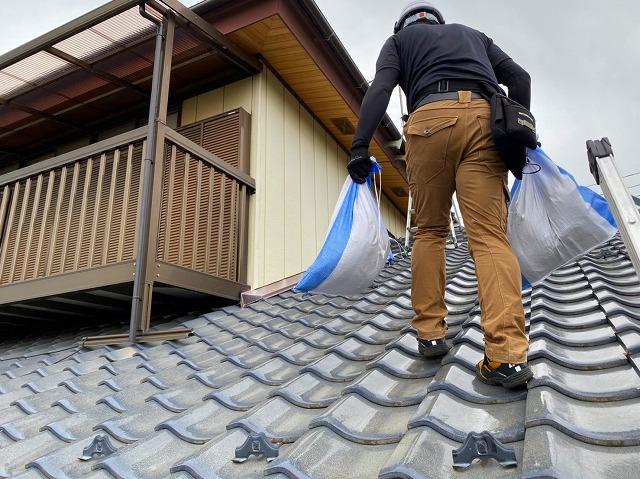 屋根の上で土嚢袋を運ぶ
