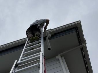 二連梯子を使用して脱落した呼び樋を運ぶスタッフ