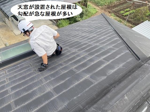 急勾配屋根に取り付けられた天窓からの雨漏りを確認するスタッフ
