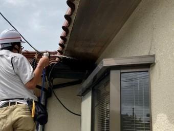 雨漏りの原因特定の為、上屋根と差し掛け屋根の間に散水を開始するスタッフ
