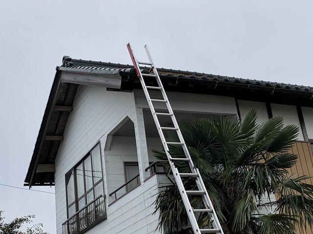二階の瓦屋根の軒先に二連梯子を掛けた様子