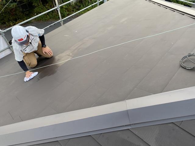 ガルバリウム鋼板でカバー工法した屋根を雑巾で拭き上げるスタッフ
