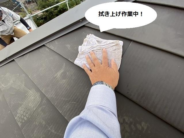 屋根の上で板金屋根を葺き上げ清掃するスタッフ