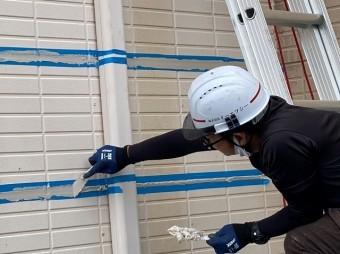 雨漏り原因のサイディング目地にシール充填を行うスタッフ