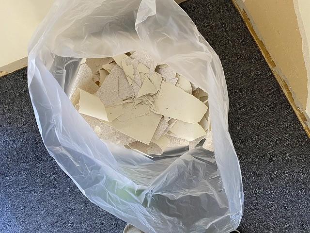 剥がした壁紙クロスをゴミ袋に集める