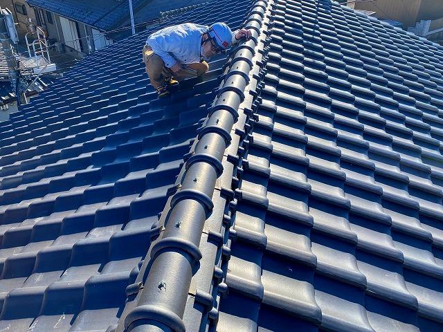 瓦屋根の棟を調査するスタッフ