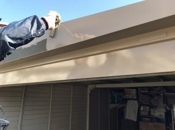 車庫の凹凸部へローラーで塗装を行う職人