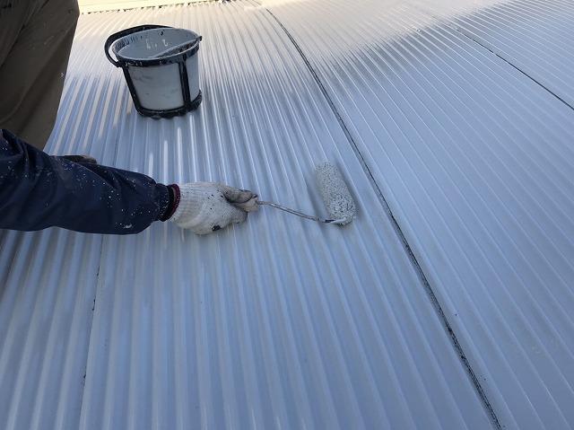 車庫のトタン屋根に塗装を行う職人