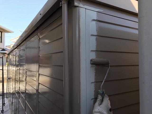 車庫の壁面にローラーで塗装を行う職人