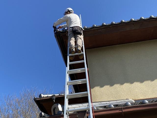 二連梯子を架け、雨樋の撤去作業を行うスタッフ