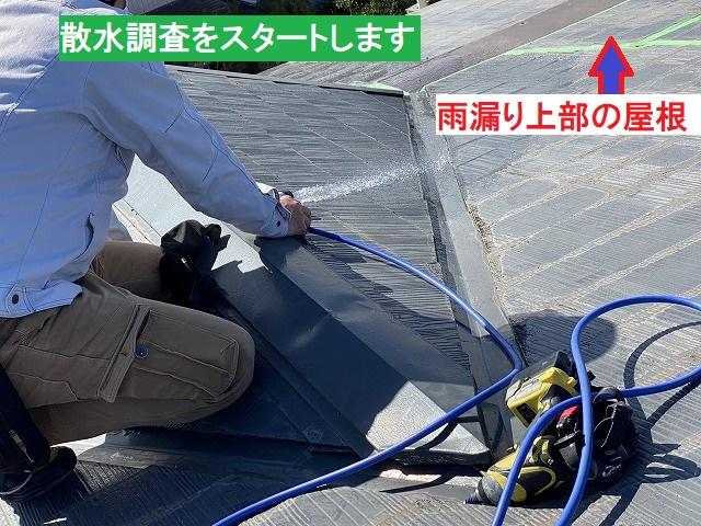 スレートコロニアル屋根へ散水を行うスタッフ