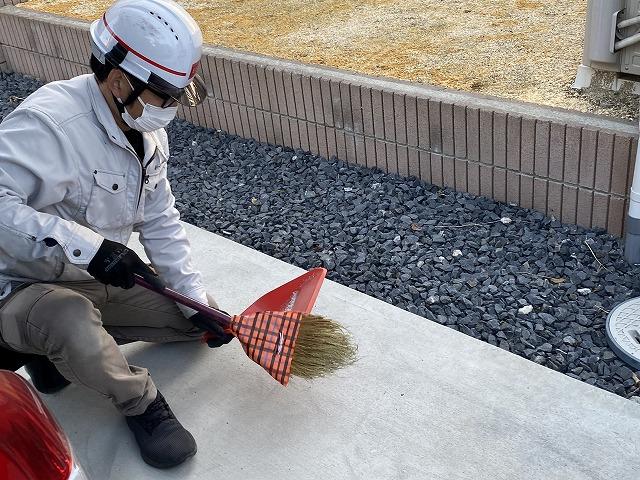作業時に出たごみを、ほうきで清掃するスタッフ