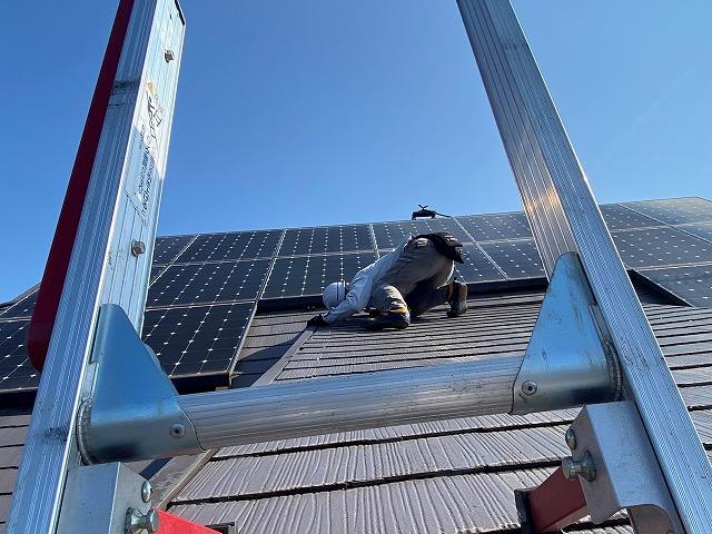太陽光の下を覗き込んで屋根の状態を確認するスタッフ