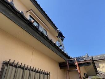 下屋根に脚立を掛け作業する職人