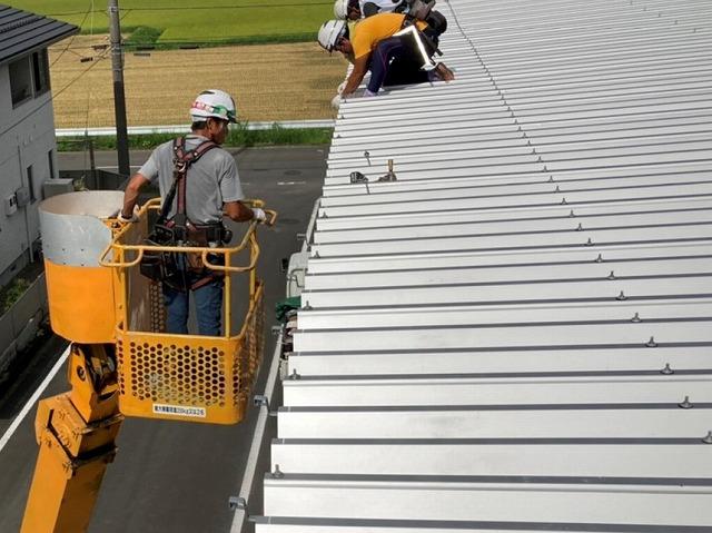 高所作業車に乗った職人と屋根上にいる職人が連携して雨樋交換作業