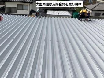 大きな折板屋根の軒先に雨どい支持金具を取り付ける作業員