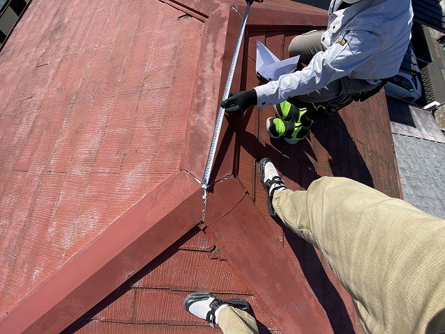 コロニアルの屋根の寸法を測る二名のスタッフ