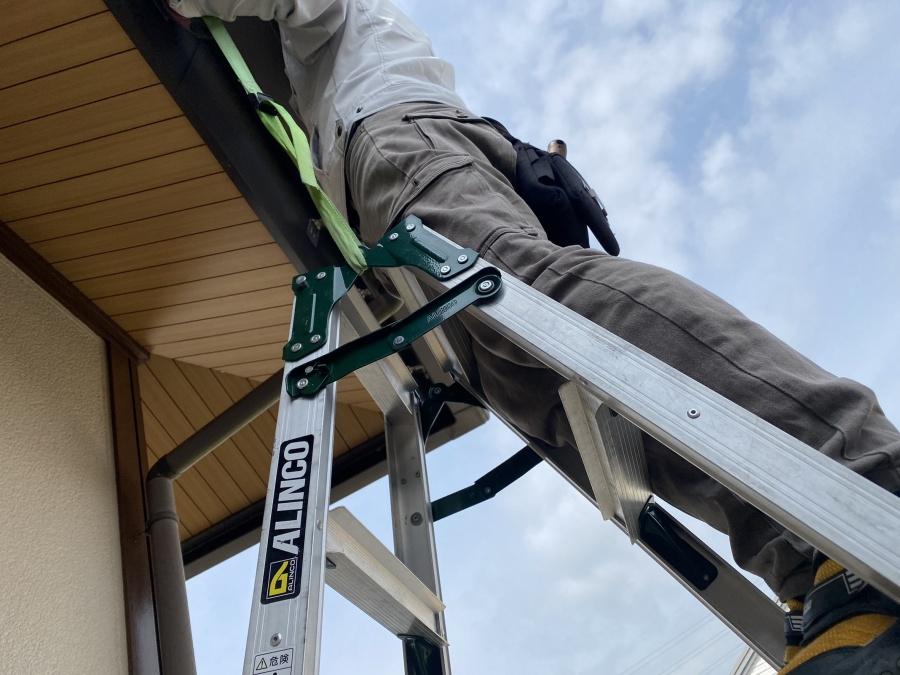 下屋根に梯子を掛け、雨樋金具にベルトで固定