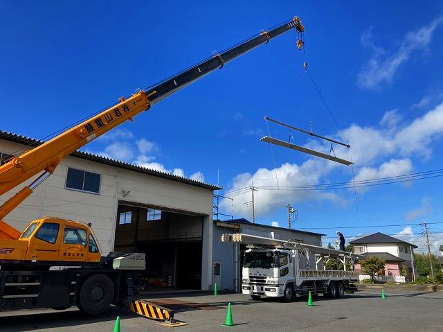 桜川市の屋根カバー工法で使用する折板屋根をクレーンで吊っている場面