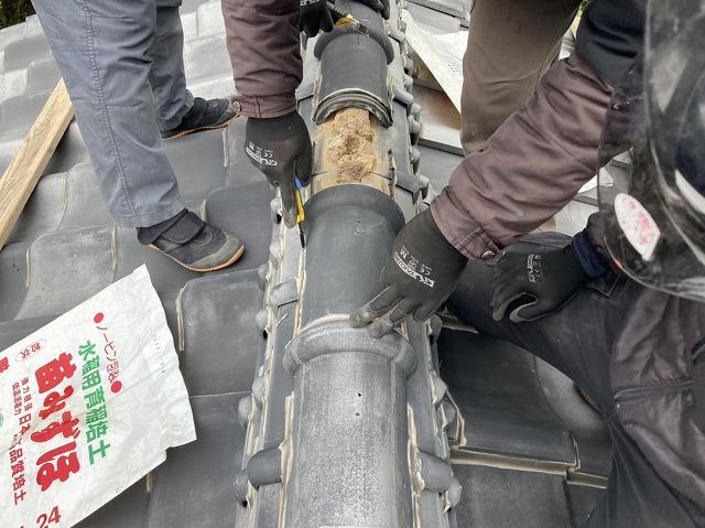 棟瓦のラバ―ロックをカッターで撤去する職人