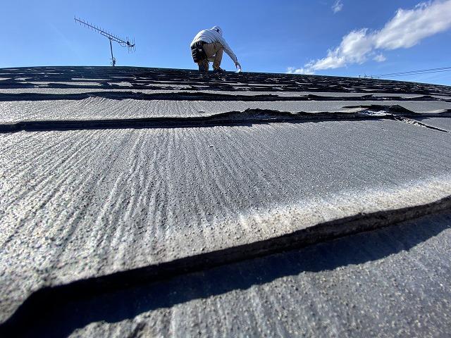 屋根上で、パミール屋根材の状態を確認しているスタッフ