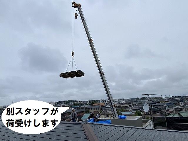クレーン車で荷揚げした屋根資材を、屋上で受け取るスタッフ