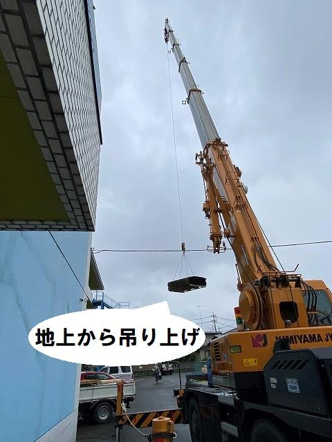 地上から屋根資材を吊り上げるラフタークレーン