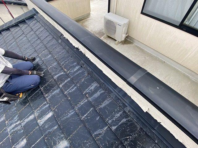 屋根の上からベランダの不具合を確認するスタッフ