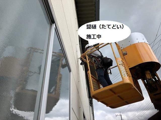 高所作業車で竪樋を施工するスタッフ
