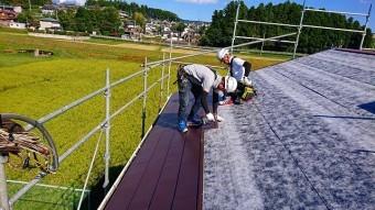 パミール屋根に金属屋根を施工中の二人の職人