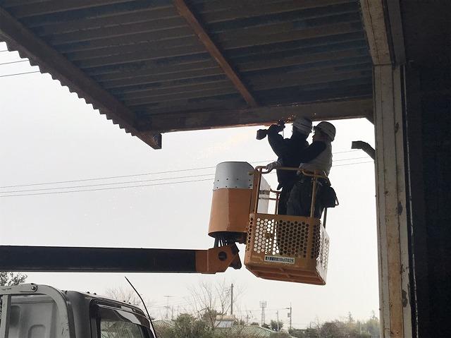 高所作業車で既存の雨樋をサンダーで切断する作業員