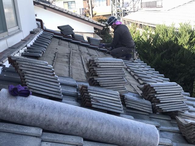 葺き直しを行うために既存の釉薬瓦を一時撤去している職人