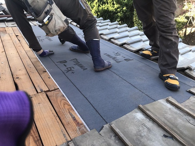 葺き直しの為野地バラ板の上に防水シートを施工し始める職人