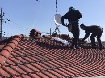 赤いモニエル瓦を解体撤去している二人の職人