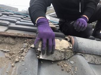 風切丸の土台にある漆喰を撤去する職人