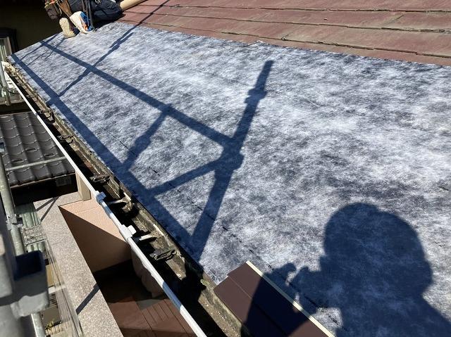 カバー工法現場で、粘着式防水シートを既存屋根に貼る