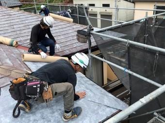 スレート屋根材に粘着防水シートを施工する複数の職人