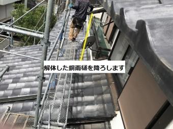解体した銅軒樋を2階から1階に降ろしている職人