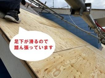 滑らないように踏ん張っている屋根職人