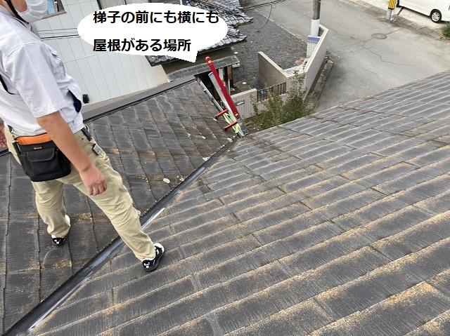 梯子から屋根に登り谷樋にまたがって立つスタッフ