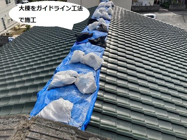 緑色の屋根瓦の棟が崩れブルーシートが養生されている