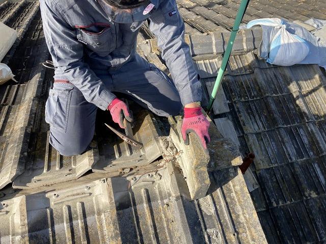 セメント瓦屋根の棟瓦を解体する職人