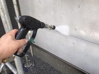 コンクリ色のサイディングに高圧洗浄をかける職人