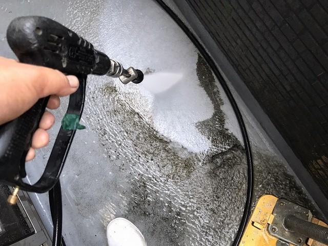 高圧洗浄をベランダの汚れに噴射する職人